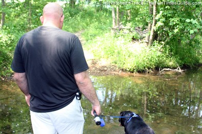 Man and dog encounter water on the Natchez Trace Parkway hiking trail.